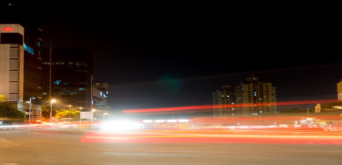 Modern buildings in Gurgaon with light trails from traffic