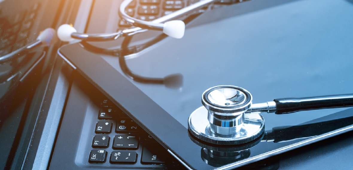 Silver stethoscope lying down on an laptop, toned blue